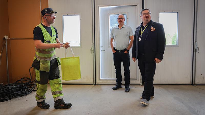 Kolme miestä seisoo yrityshallissa.
