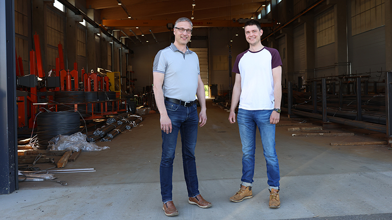 Kaksi miestä seisoo teollisuushallin edessä.