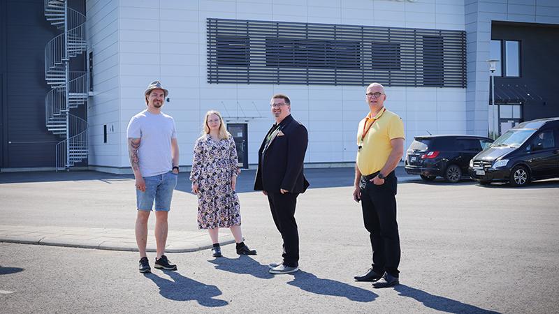 Neljä henkilöä seisoo parkkipaikalla.