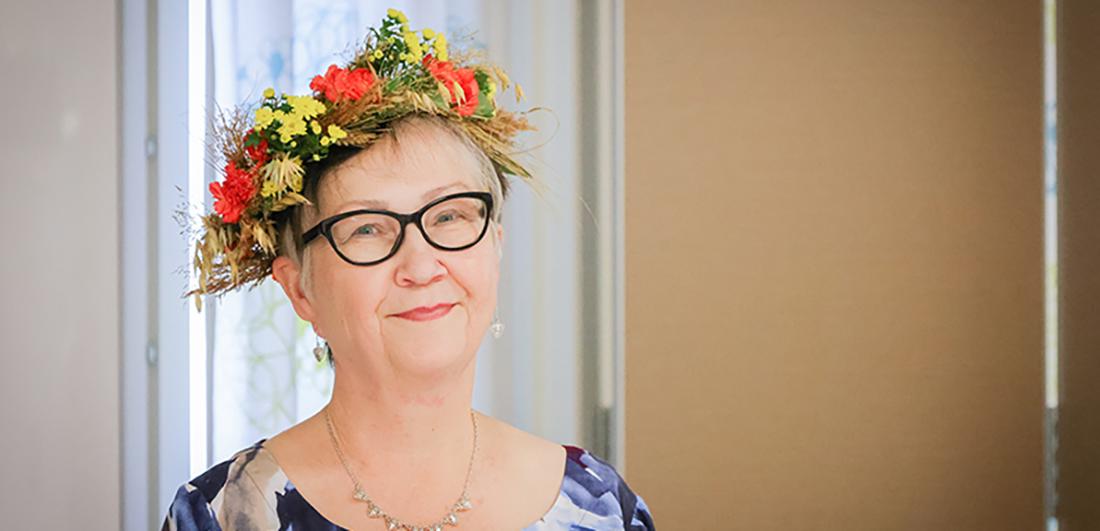 Maire Taikina-aho eläkejuhlissaan kukkaseppele päässä.