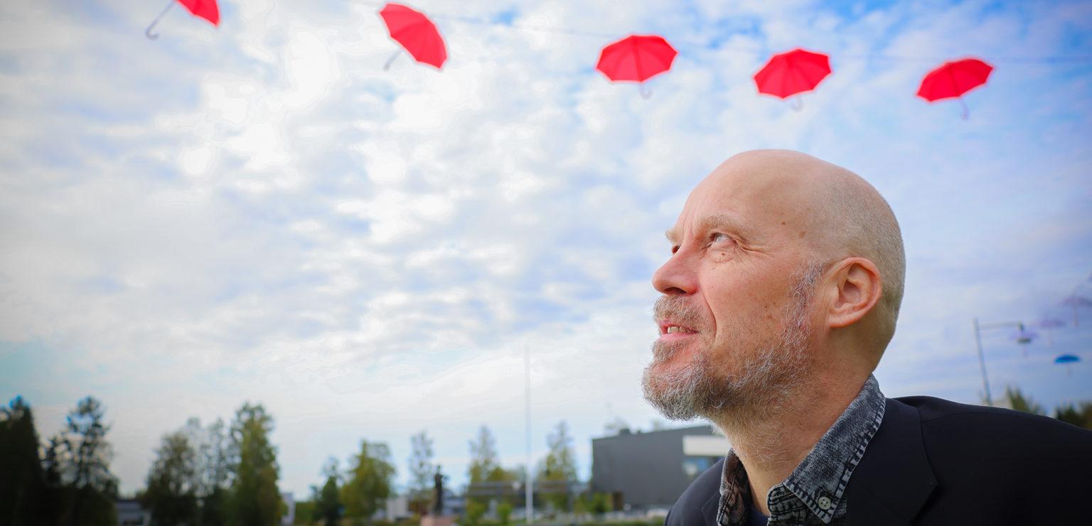 Kirjasto- ja kulttuurijohtaja Janne Nevala seisoo Liminganraitilla LimmiFestiä koristavien punaisten sateenvarjojen alla.