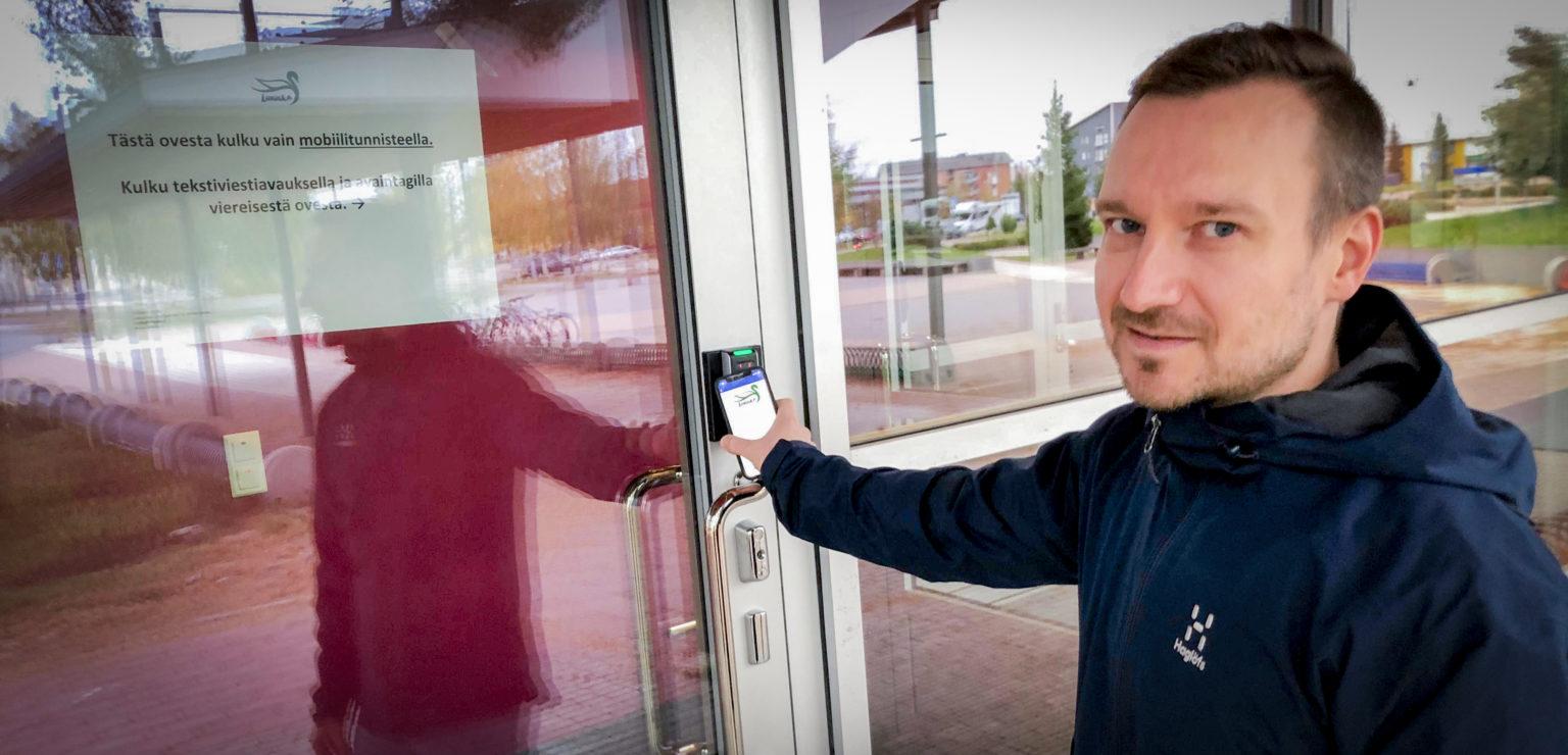 Liikuntapalvelupäällikkö Janne Laamanen avaa kuntosalin ovea älypuhelimellaan.