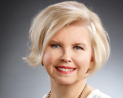 Vaaleahiuksinen nainen hymyilee kuvassa.