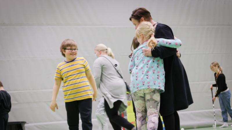 Lapsi halaa ohjaajaa Unelmien liikuntapäivä -tapahtumassa.. Kuvassa etualalla Eelis Vesterinen, Neea Ristikari ja Auli Kauranen.
