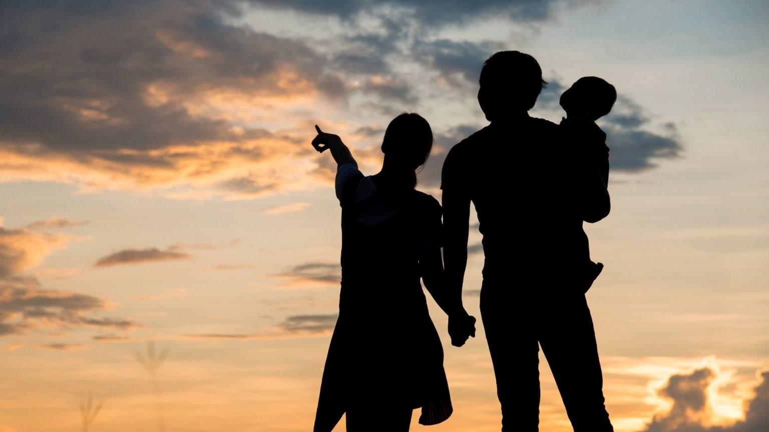 Pariskunta seisoo ilta-auringossa lapsi sylissä.