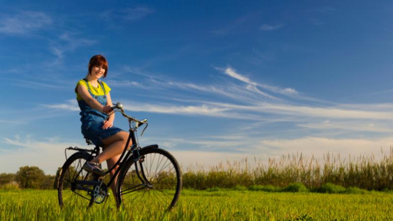 Tyttö pyöräilee peltomaisemassa.