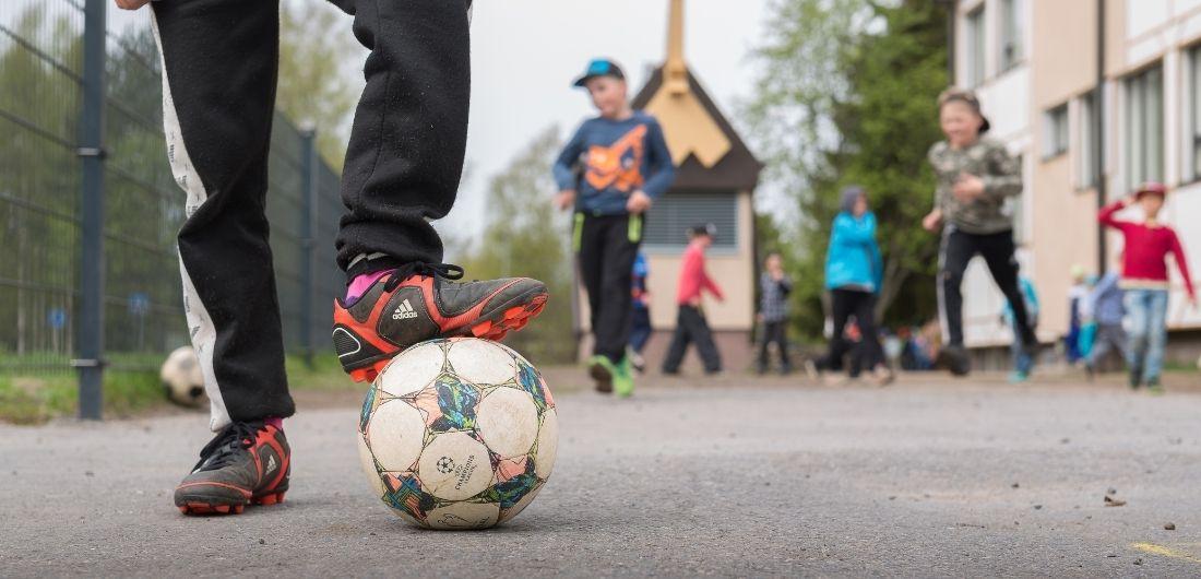 Koululaiset pelaavat jalkapalloa.