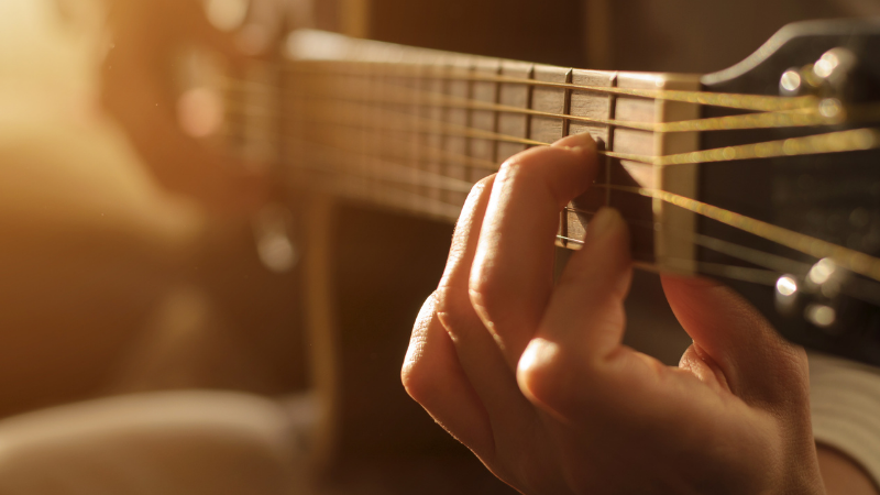 Sormet akustisen kitaran kielillä.
