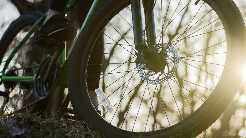 Aurinko siivilöityy maastopyörän eturenkaan lävitse.