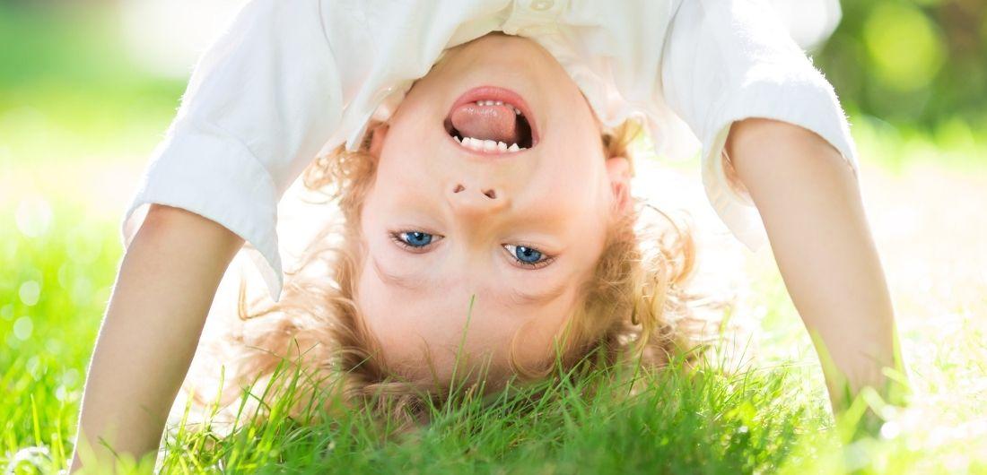 Lapsi pää alaspäin nurmikolla.