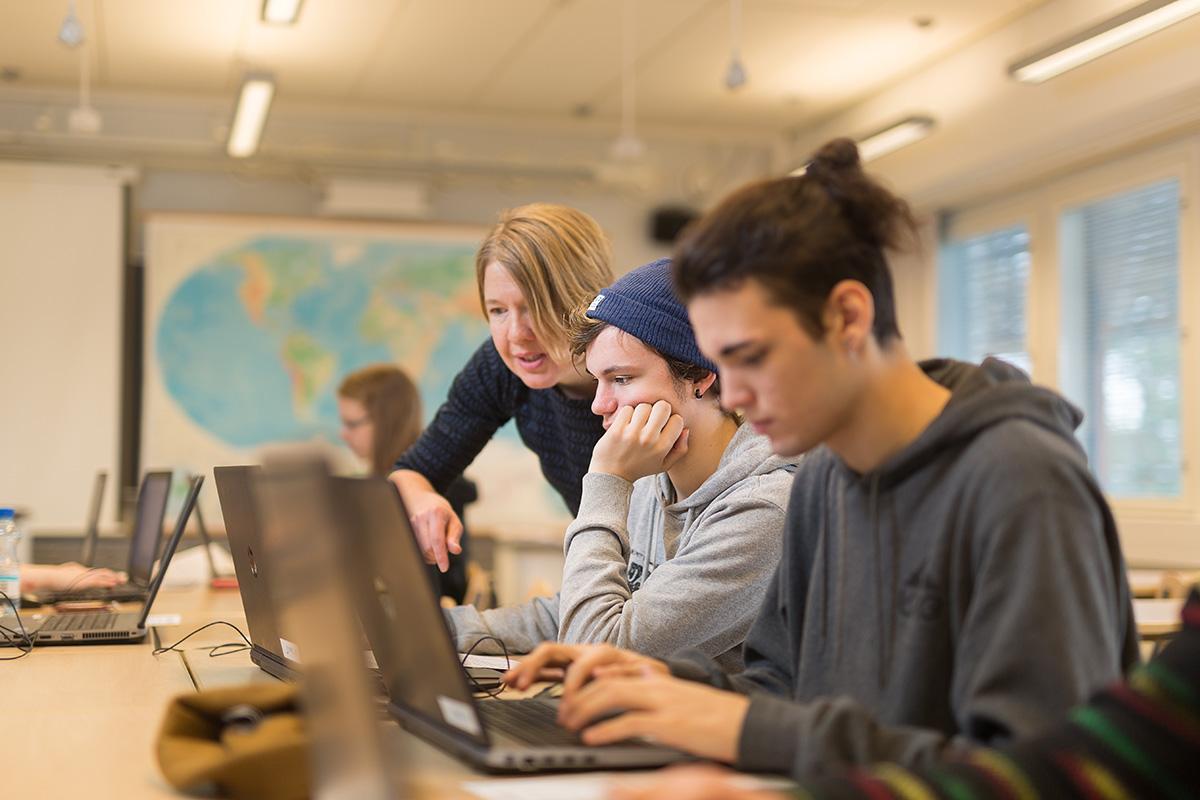 Opiskelijat työskentelevät kannettavilla tietokoneillaan opettajan ohjauksessa.