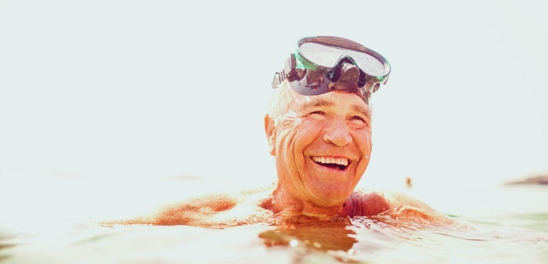 Mies on uimassa ja hymyilee uimalasit otsallaan.