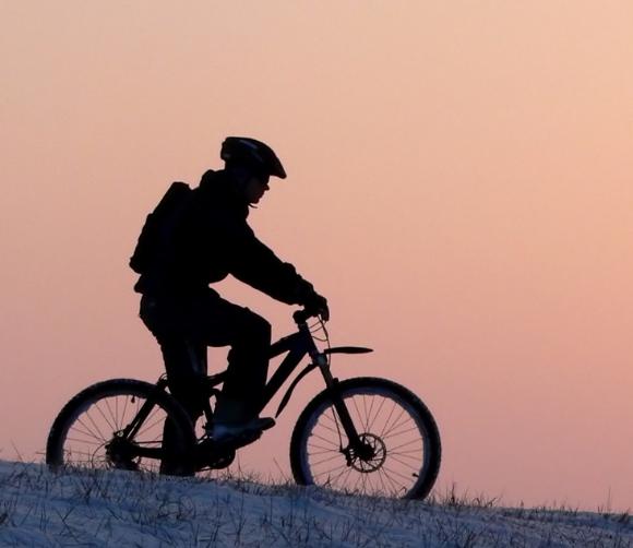 Pyöräilijä talvisessa maisemassa.
